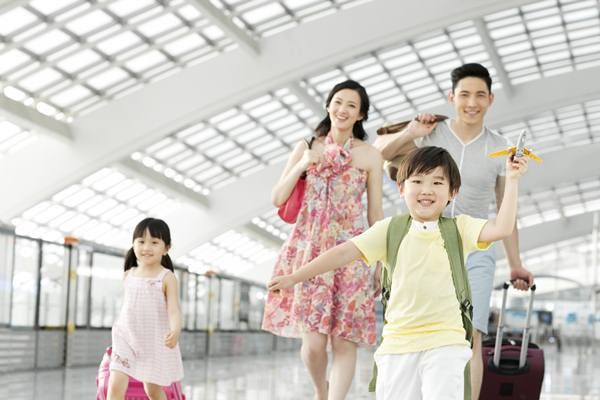 25 May 2013 --- Happy family with luggage at the airport --- Image by © Blue Jean Images/Corbis