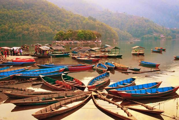 POKHARA, NEPAL - MARCH 30: Unidentified tourists do boating on Fewa (Phewa) lake on March 30, 2014 in Pokhara, Nepal. Pokhara is a popular tourist destination in Nepal.