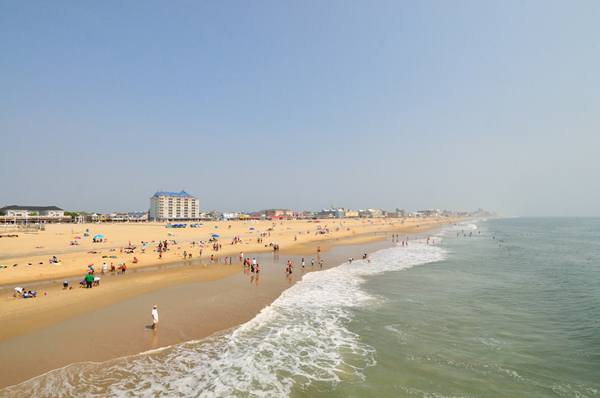 A view up the beach at Ocean City Maryland on a bright but hazy morning with vacationers sunbathing, strolling on the beach and wading in the surf.